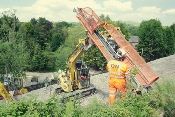 Soil nailing rail embankment with remote control rigs
